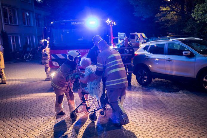 De brandweer evacueert een bewoner