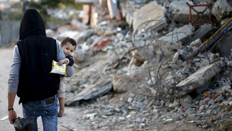 Een Palestijn loopt langs een huis dat is vernietigd tijdens een bombardement. Beeld reuters