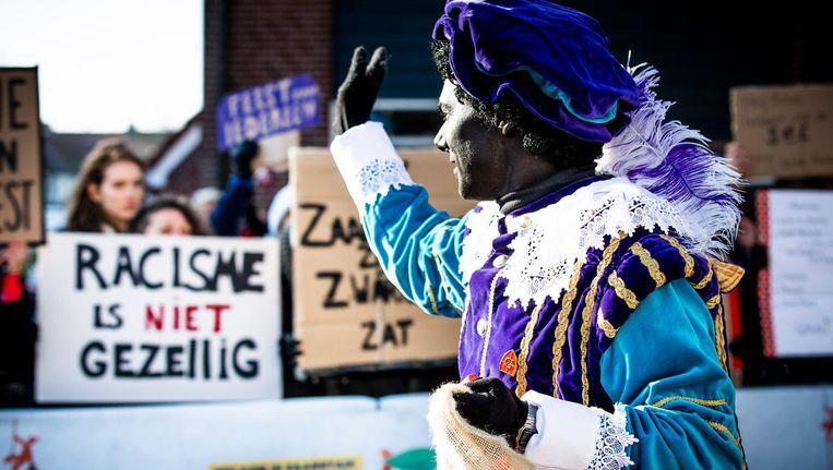Demonstranten en een Zwarte Piet tijdens de landelijke intocht van Sinterklaas op de Zaanse Schans. Beeld ANP