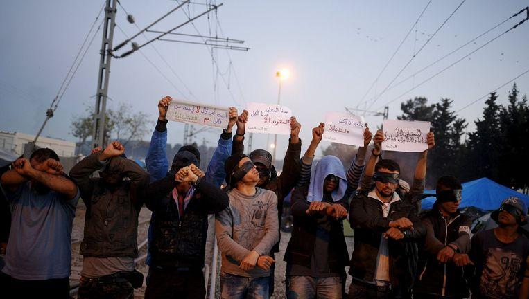 Een demonstratie in een vluchtelingenkamp aan de grens tussen Griekenland en Macedonië. Beeld reuters