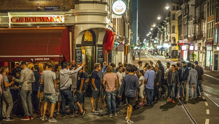 De gasten van café Bouwman in de Utrechtsestraat zijn 'uitgewaaierd' tot op de rijbaan. Ze moeten naar binnen. Beeld Amaury Miller (www.amaurymiller.nl)