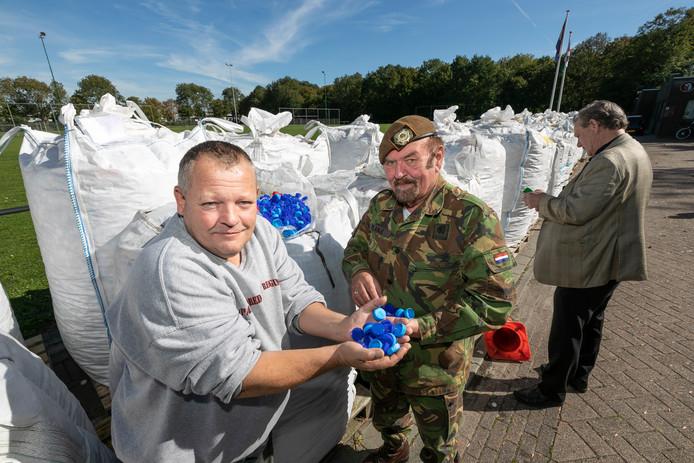Voorzitter/veteraan Jeroen Stam (links) van Ouwestomp en Chris Planje bij de twintig ton ingezamelde uitgesorteerde dopjes voor een speciale actie bij het veteranencentrum.