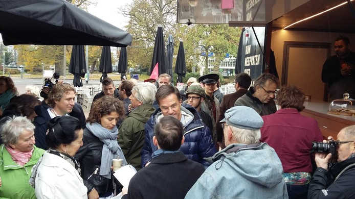 De minister-president in Arnhem, omgeven door bewonderaars en vragenstellers.