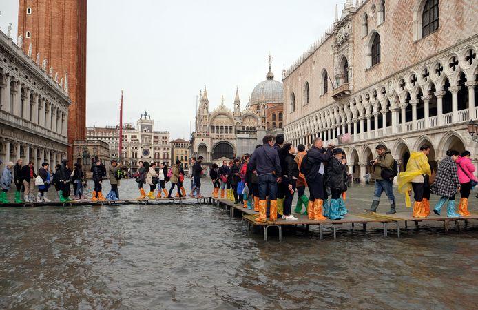 Met provisorische bruggetjes en plastic zakken om de schoenen proberen de toeristen de voeten droog te houden aan het Dogepaleis.