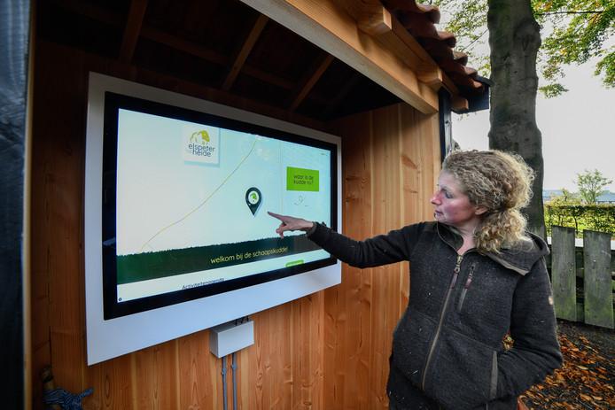 Herder Daphne van Zomeren wijst naar de locatie van de kudde, die is te zien op het nieuwe informatiepaneel.