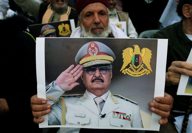 Een man houdt een foto van Khalifa Haftar omhoog tijdens een demonstratie in Tripoli.