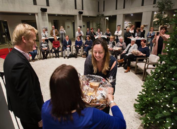 Carlijn van Esch, vrijwilliger op peuterspeelzaal 't Keike in Liessel, krijgt een cadeaupakket van de gemeente Deurne als dank voor haar inzet.