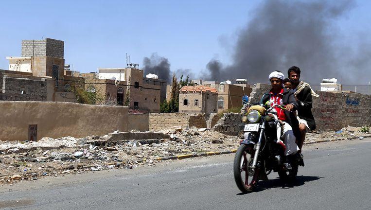 Jemenieten in Sanaa vluchten van de plek waar een aanval van de door Saoedi-Arabië geleide coalitie heeft plaatsgevonden. Beeld epa