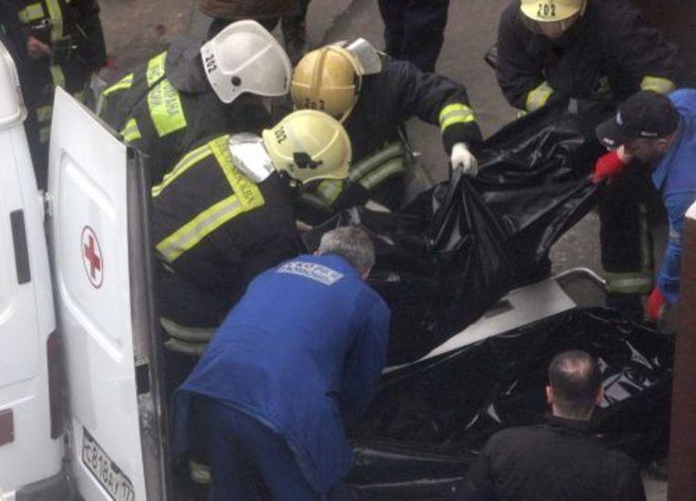 Reddingswerkers dragen een lichaam weg bij metrostation Park Koltoeri, vlak na de aanslagen. ANP Beeld