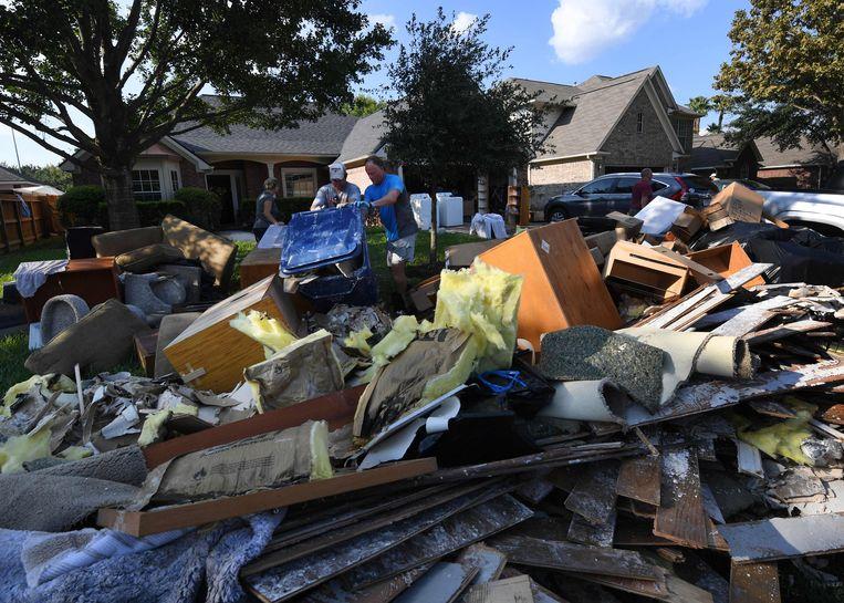 Bewoners van Houston ruimen de troep op die het gevolg is van orkaan Harvey, 31 augustus 2017. Beeld AFP