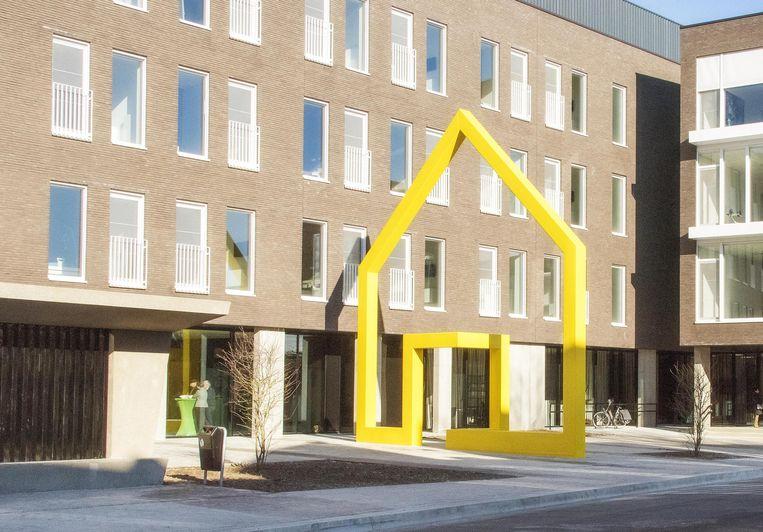 Het Gele Huis in de voortuin van het nieuwe gebouw valt fel op.