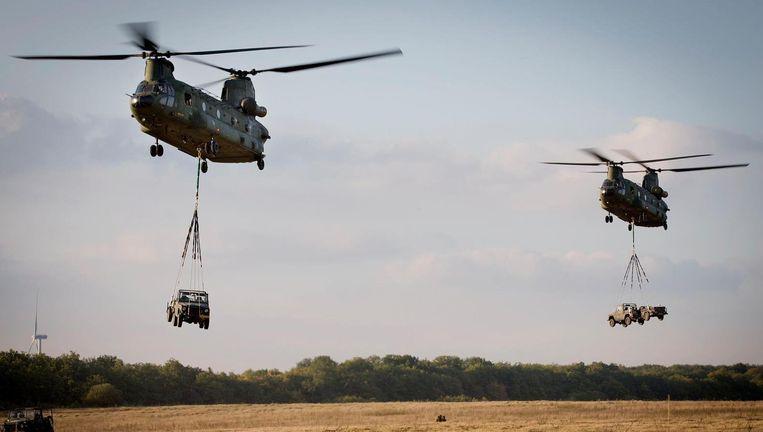 Twee Chinook-transporthelikopters verplaatsen jeeps. Beeld ANP