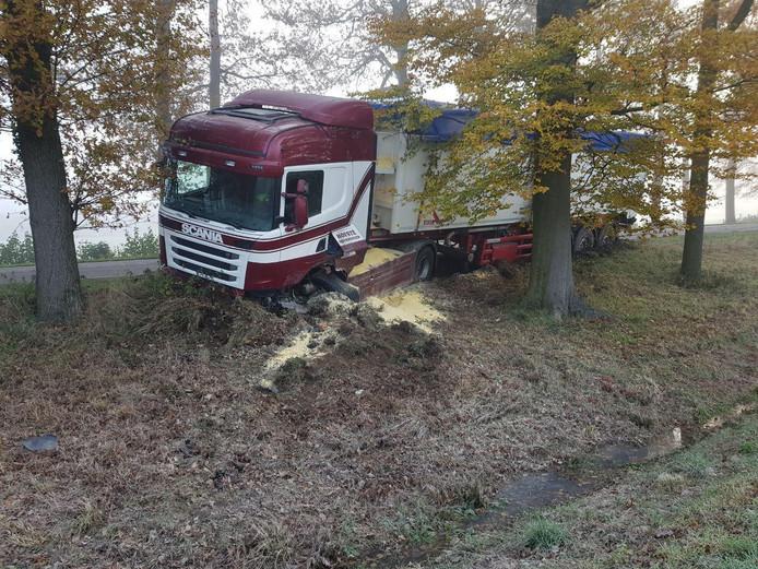 De vrachtwagen kwam tussen de bomen tot stilstand.