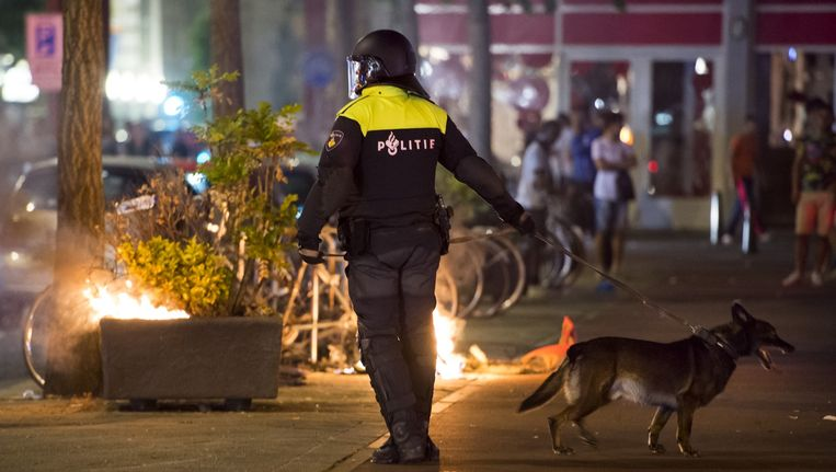 Agenten en leden van de Mobiele Eenheid (ME) op straat in de Haagse Schilderswijk waar begin deze maand rellen uitbraken. Beeld anp