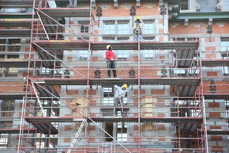 Gespecialiseerde arbeiders aan het werk aan de gevel.