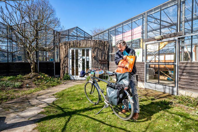 Een klant doet zijn spullen in een fietstas die hij net heeft gekocht bij de tuinderij Beeld Raymond Rutting / de Volkskrant