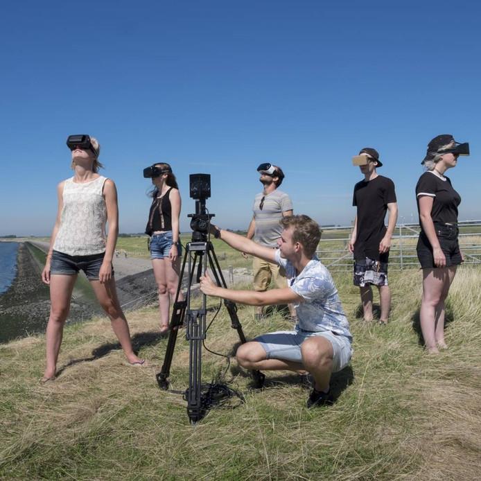 Onderzoek in de buitenlucht naar virtual reality. Filmmaker/docent Wietske de Klerk (links) laat haar studenten, die een speciale bril dragen, zien wat mogelijk is. In het midden staat een 360°-camera opgesteld.