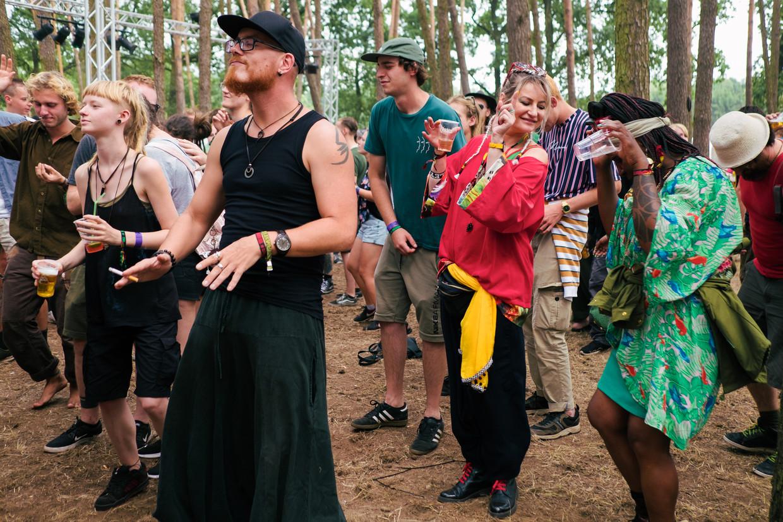 Mensen van alle slag vermaken zich in het dub-bos. Hoewel de muziek er amper varieerde, stond het er bomvol. Beeld Damon De Backer