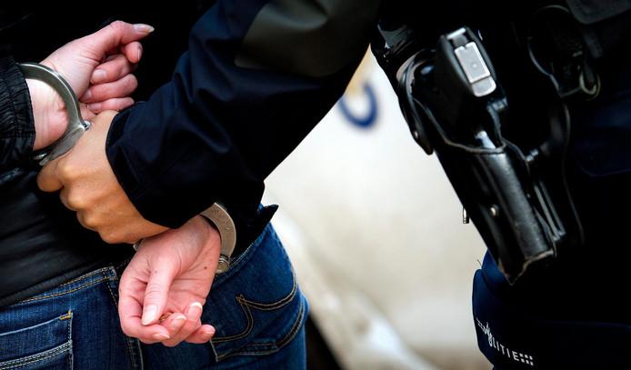 2015-01-22 12:54:29 GRONINGEN - Een politieagent voert een verdachte af. Aanhouding, arrestatie, handboeien, politie, agent, agenten. ANP XTRA KOEN VAN WEEL