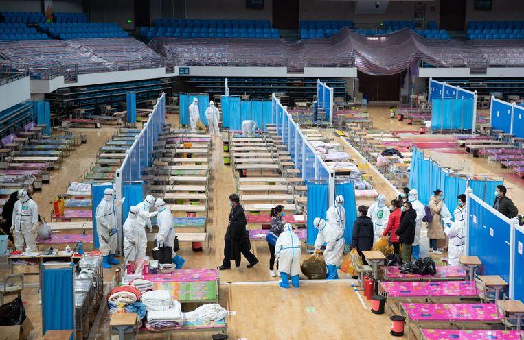 Medewerkers ruimen het noodhospitaal in de sporthal van Wuchang op.   Beeld EPA