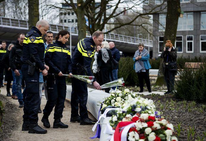 Mensen leggen bloemen op het 24 Oktoberplein, een jaar nadat hier de tramaanslag plaatsvond.