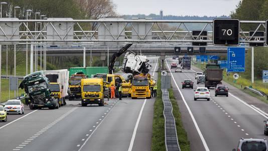 De ravage op de A12 bij Zevenaar wordt opgeruimd na het grote ongeval tussen drie vrachtwagens, een busje en een auto, dinsdagmorgen.