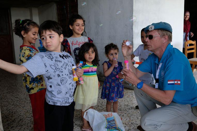 Unifil-veteraan Richard Vermeulen blaast bellen met Libanese kinderen in het zuiden van het land, voor wie hij cadeautjes heeft meegebracht.  Beeld Gert Jan Rohmensen