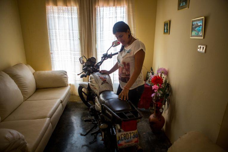 Rosandinella Casares in haar woning in La Vela de Coro met de taxi-motor waarmee haar man Junior Díaz 'bijna niks meer' verdiende. Beeld Manaure Quintero