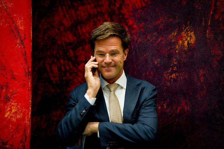 Premier Rutte aan de telefoon in de Tweede Kamer. Beeld ANP