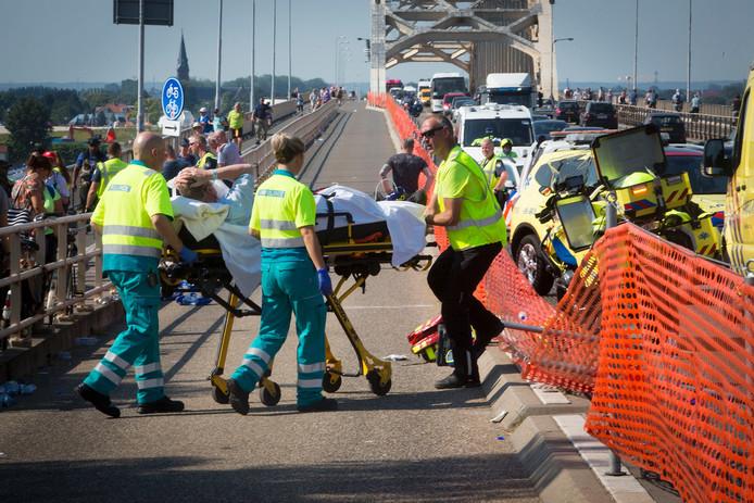 Een Vierdaagsewandelaar wordt door ambulancemedewerkers meegenomen.