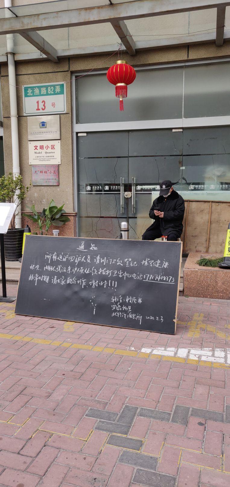 In buurt Xinjing nr 2. in Shanghai houdt een buurtbewaker de wacht bij de ingang van de wijk. Op het bod staan gedragsregels voor de bewoners.  Beeld Eefje Rammeloo