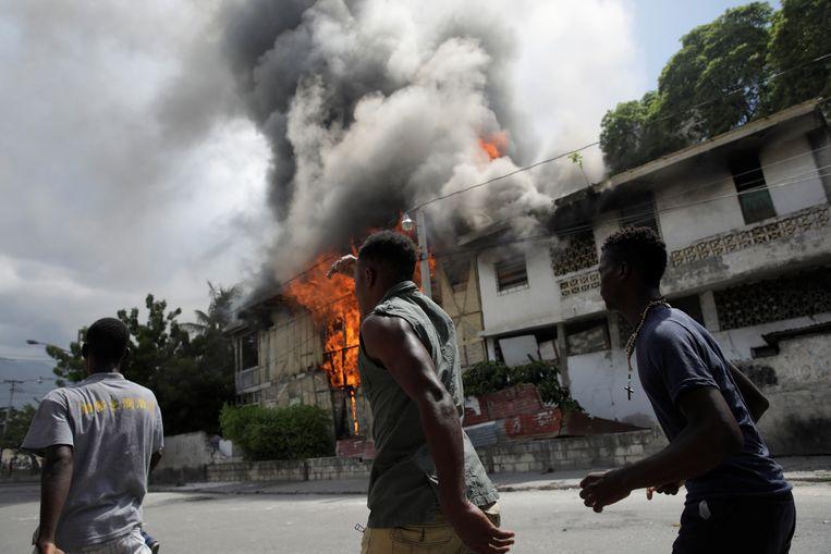 Demonstranten lopen langs een brandend huis in Port-au-Prince in Haïti.