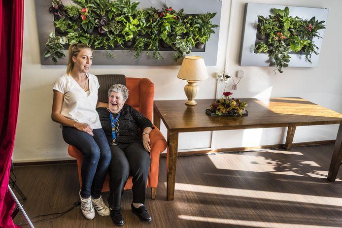 Mevrouw de Jong en medewerkster Marie Louise Hannenberg genieten van de groene wand op de gesloten afdeling van De Posten in Enschede.