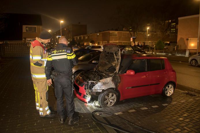 Autobrand in de Utrechtse wijk Kanaleneiland. Brandweermannen nemen de schade op.