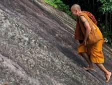Un moine escalade une paroi rocheuse pieds nus devant des grimpeurs sous le choc