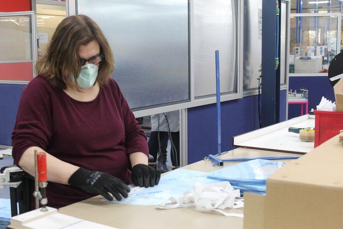 Een medewerker van WSD in Boxtel stelt een gezichtsbeschermer samen.