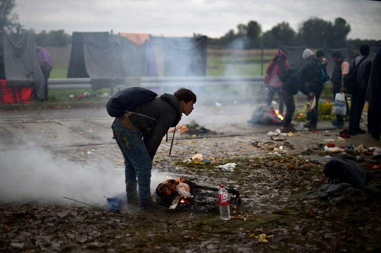 Eem migrant in Trnovec, Kroatië, houdt zich warm bij een vuurtje. Beeld getty