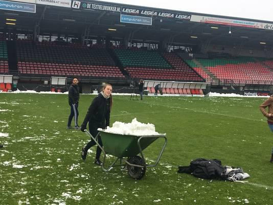 Zo'n honderd vrijwilligers helpen deze vrijdag mee met het sneeuwvrij maken van het veld, waarop vanavond de wedstrijd NEC–Jong FC Utrecht wordt gespeeld.