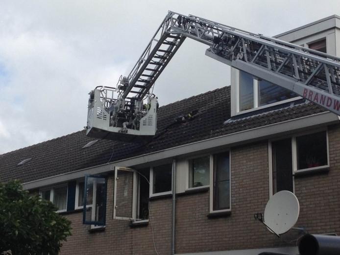 Gat in het dak bij de brand in de Stikkerstraat.