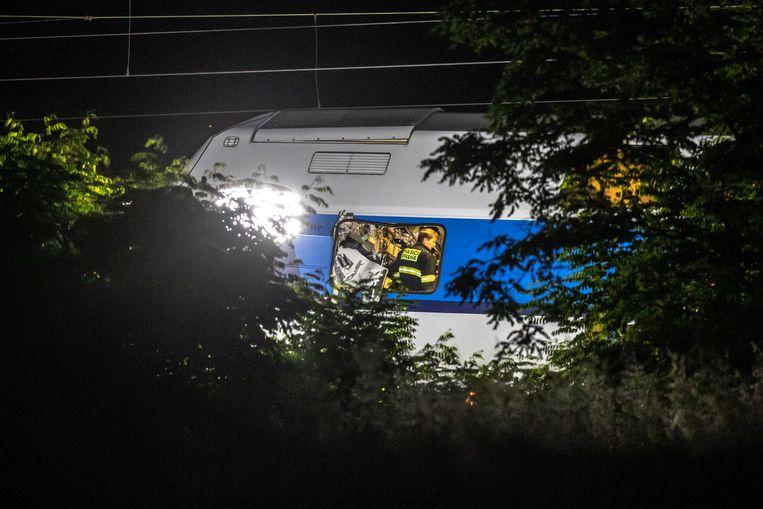 Hulpverleners bij de wrakken van de twee gebotste treinen.
