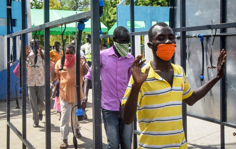 Passagiers van een ferriedienst in het Keniase Mombasa moeten door een poort waar ze allemaal worden gedesinfecteerd. Beeld AP