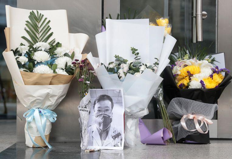 Mensen leggen bloemen neer bij het ziekenhuis in Wuhan waar de arts is gestorven.