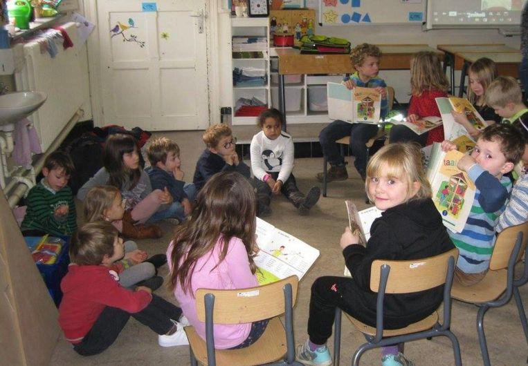 De leerlingen van het eerste leerjaar lezen het sprookje van Hansje en Grietje voor aan de kinderen van het derde kleuterklasje.