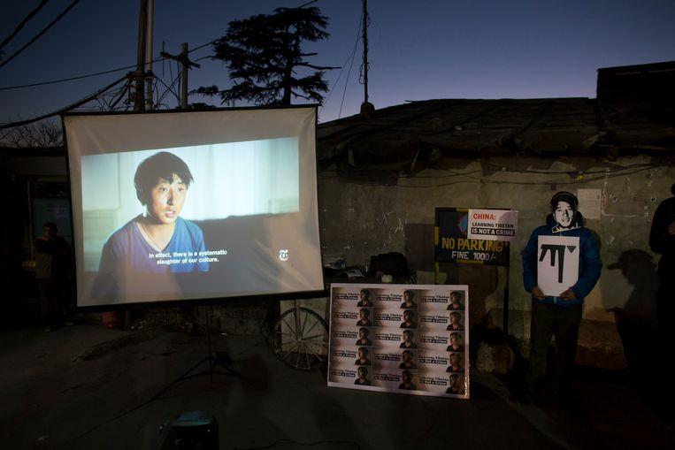 Een Tibetaanse activist, in ballingschap in India, staat met een masker van de gevangen gezette Tashi Wangchuk bij een scherm waarop de documentaire met Tashi Wangchuk wordt afgespeeld, in januari 2018.  Beeld AP