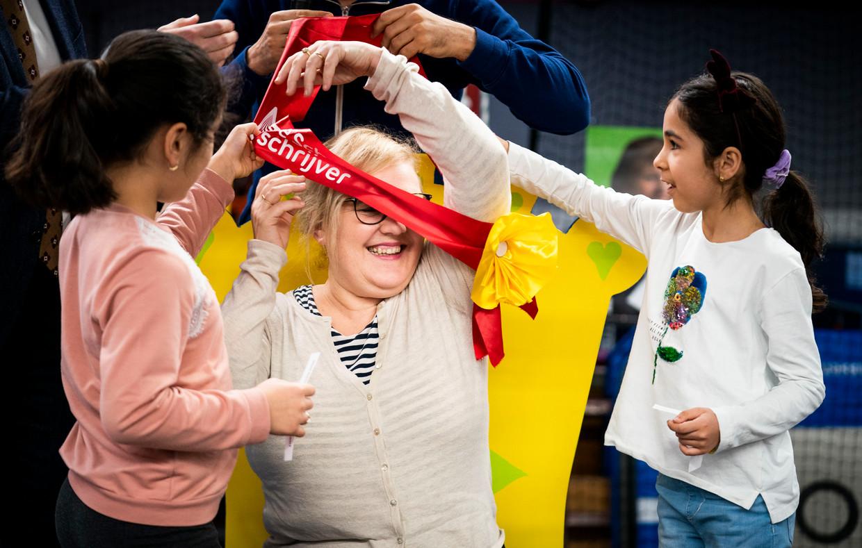 Kinderboekenambassadeur Manon Sikkel krijgt van leerlingen van openbare basisschool Het Startpunt in Den Haag een sjerp omgehangen tijdens de start van de tiende editie van De Schoolschrijver. Beeld null