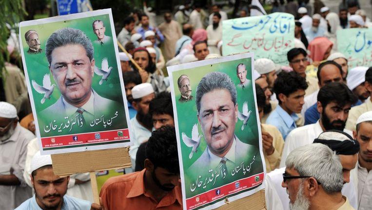 Demonstranten met een beeltenis van Khan. Beeld afp