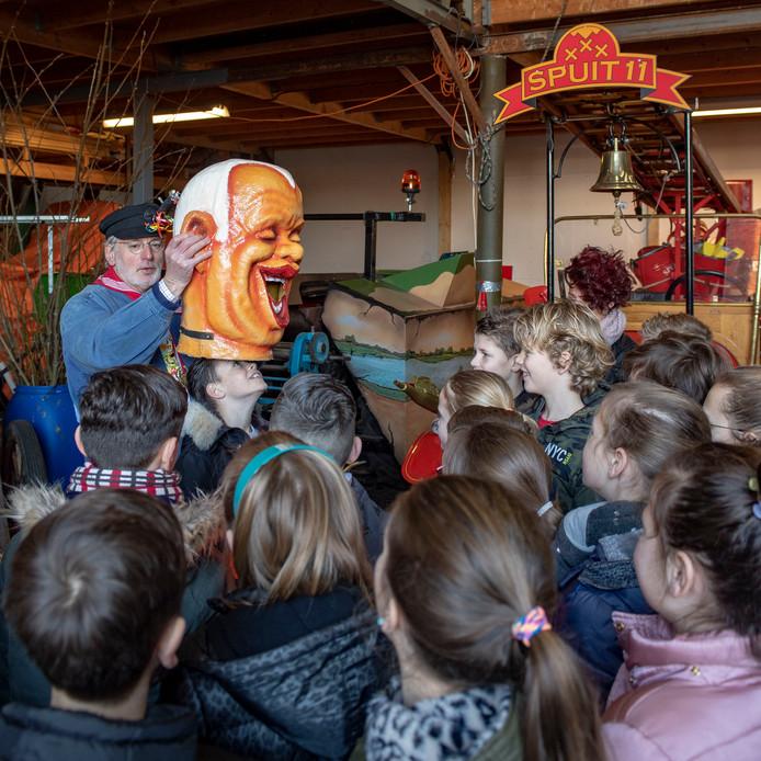 """Schoolkids bezoeken Halwana (bouwclubs). Boer Willem laat de kinderen nadat ze spuit ellef hebben kunnen bewonderen, één voor één een zogeheten """"Gaper""""  opzetten."""