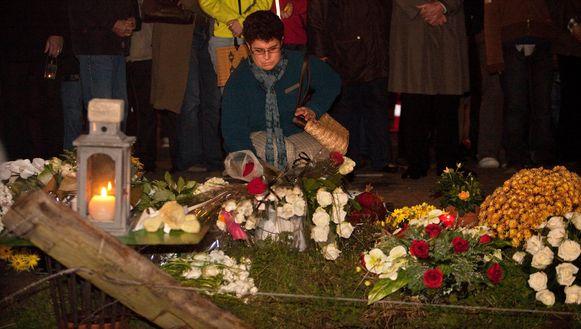 Een vrouw legt bloemen neer op de plaats waar de tragische gebeurtenis zich afspeelde.