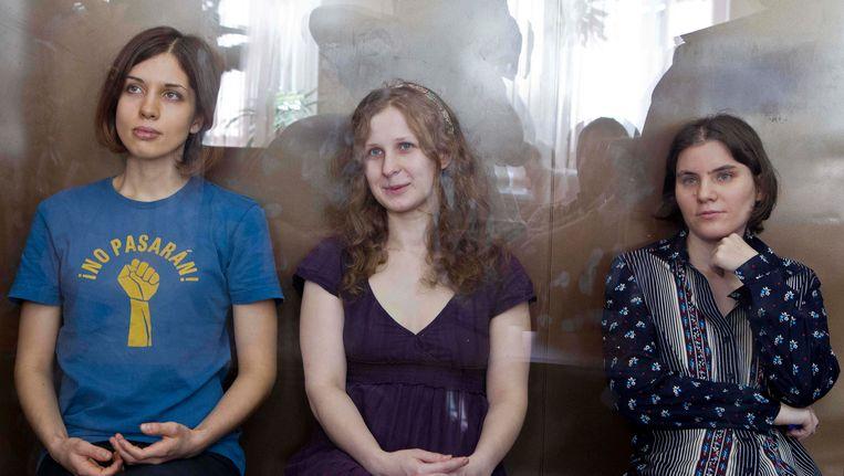 Bandleden Nadezhda Tolokonnikova, Maria Alekhina en Yekaterina Samutsevich van Pussy Riot achter het glas in de rechtbank. Beeld AP