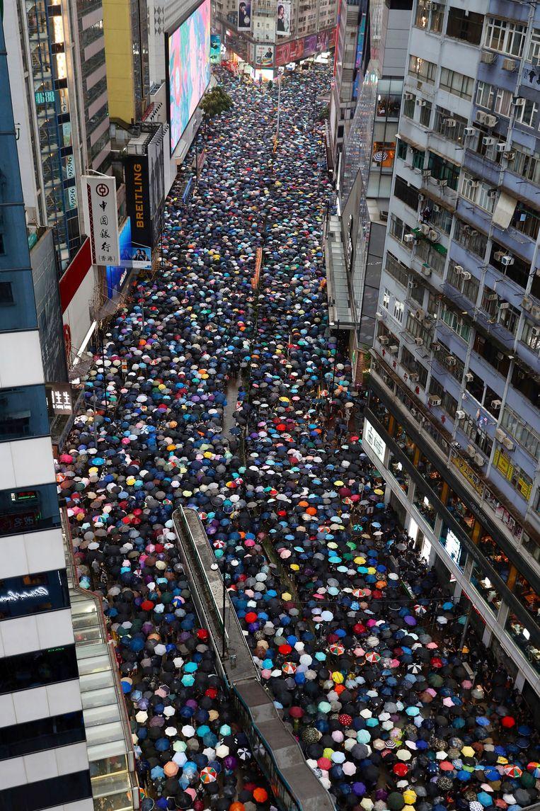 Betogers in de straten van Hongkong op zondag 18 augustus, met paraplu's tegen de ongenadig harde regen. Beeld AP